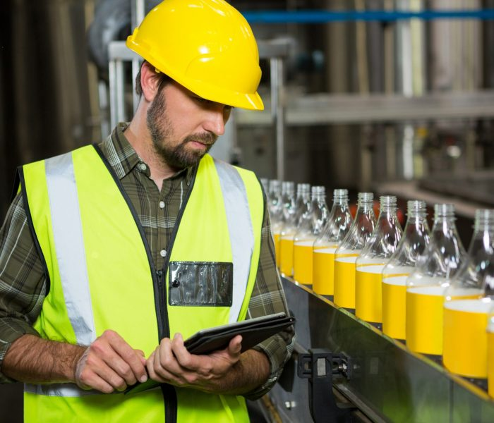 Man with smartpad in juice produciton - pikwizard-7b67b0f112da87a98366fd7d1dfe7714